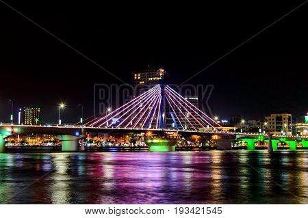 Cable-stayed bridge in the night in Da Nang city Vietnam. Multi-colored illumination of the bridge.