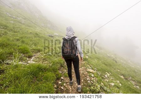 Tourist lost in the fog high in the mountain. Alone young woman with backpack seen from her back inside dense mist.