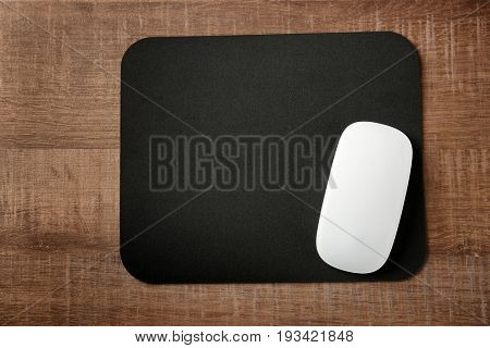 Pad with computer mouse on wooden table
