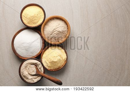Wooden bowls with different types of flour on table
