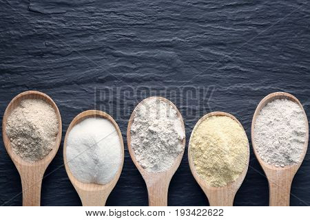 Wooden spoons with different types of flour on dark background