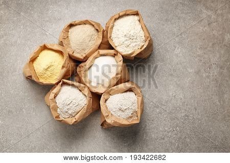 Paper bags with different types of flour on table