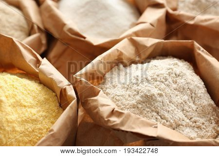 Paper bags with different types of flour, closeup