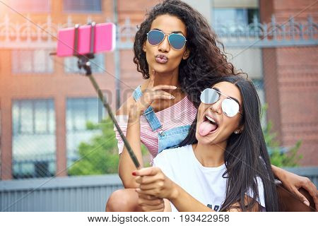Two smiling young women sitting on a city bench making faces while taking self portraits together with a smartphone and selfie stick