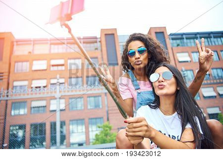 Two laughing young women sitting on a city bench making faces while taking self portraits together with a smartphone and selfie stick