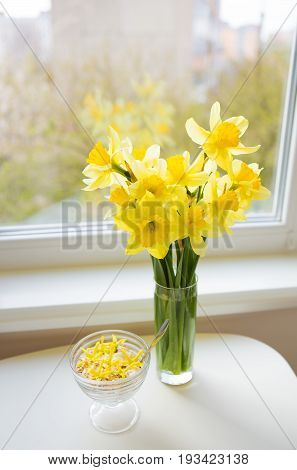 Posy of bright yellow daffodils on white wooden table