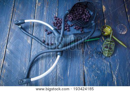 Sports slingshot, feeding feeders, hooks, pellets. Carp fishing.