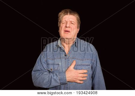 Portrait of old man suffering chest pain on black background