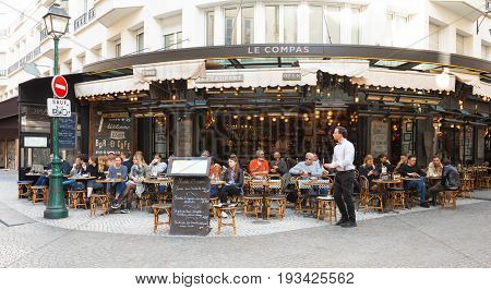 PARIS - MARCH 27, 2017: People have lunch at one of the traditional French bistro in Paris. Restaurant Le Compas is also in the view on March 27, 2017.
