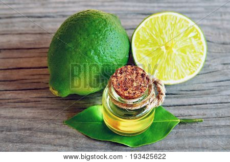 Lime essential oil in a glass bottle with fresh lime fruits.Lime oil for spa,aromatherapy and bodycare.Extract oil of lime.Selective focus.