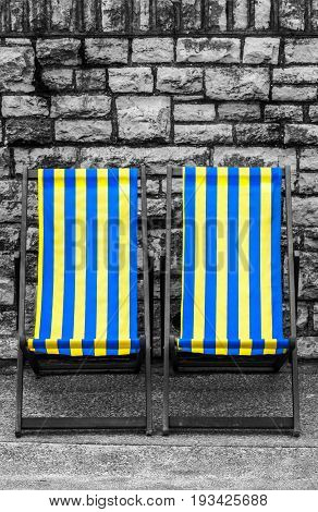 Empty yellow and blue striped deckchairs, Bournemouth, England