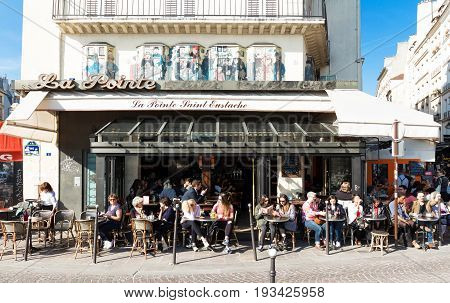 PARIS - MARCH 27, 2017: People have lunch at one of the traditional French bistro in Paris. Restaurant Le pointe Sainte Eustache is also in the view on March 27, 2017.