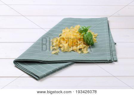 pile of quadretti - square shaped pasta on grey place mat