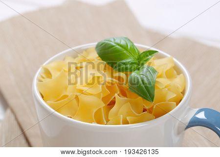 mug of quadretti - square shaped pasta on beige place mat - close up