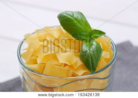 glass of quadretti - square shaped pasta on grey place mat - close up