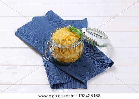jar of quadretti - square shaped pasta on blue place mat