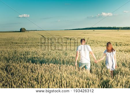 Fall in love with the field. The guy and the girl are holding hands at the talk of the sun.