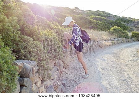 Young woman with white hat tying shoelace, hot summer in Kolokitha island, Crete, Greece