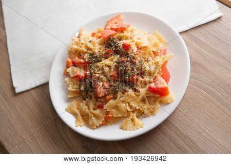 farfalle with tomato and paprika on wooden table