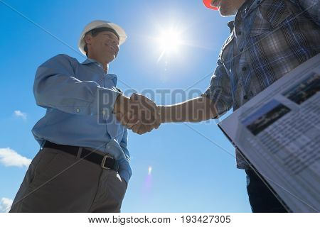 Builders Handshake, Architect And Contractor Agreement During Meeting Discussing Blueprint Buiding Plan