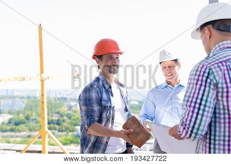 Team Of Builders On Construction Site, Contractor Giving Apprentice Brick New Building Project Start Concept