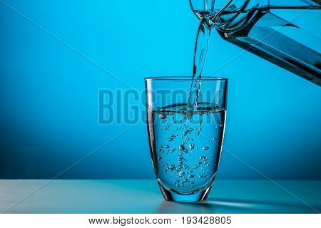 Man pours water from glass into glass on blue background in studio