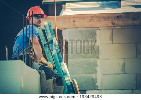 Resting Caucasian Worker on the Edge of Building Element.