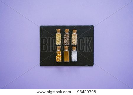 Miniature glass jars with different cereals papper tea coffee beans pasta and salt on black stone substrate with lilac background