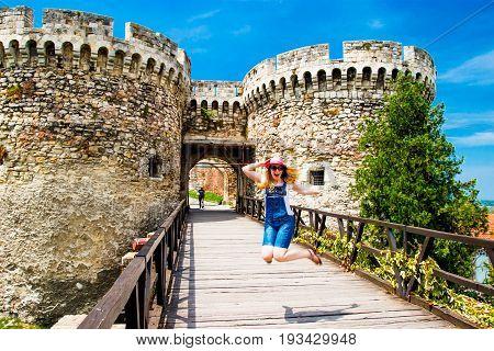 Girl jumping near Belgrade Serbia Old Castle Entrance poster