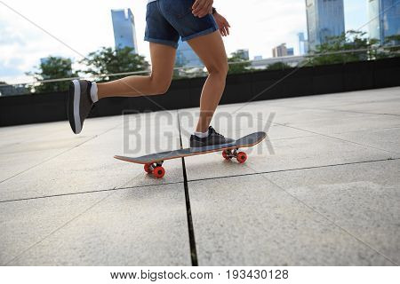 young woman skateboarder riding skateboard at city