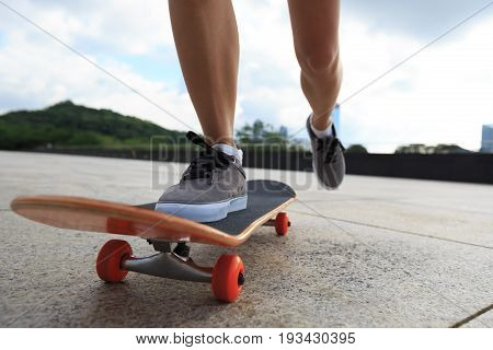 young woman skateboarder legs skateboarding at city