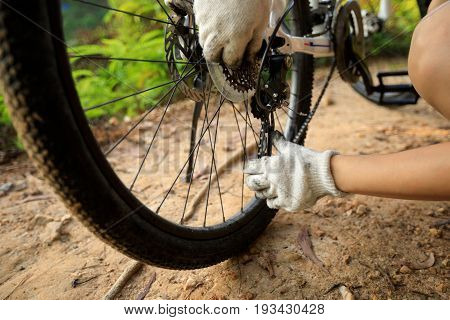 mountain biker fixing the bike chain on forest trail