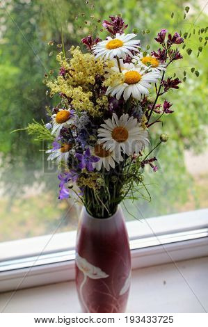 Elegant ikebana from wildflowers in a vase on the windowsill.