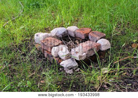A small hearth for a fire in a forest built of red brick.