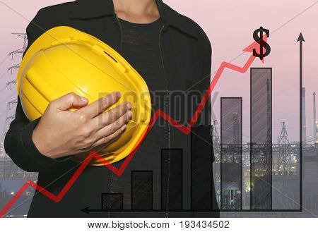 business woman hug a yellow helmet on power plant background and bar graph in concept of profit and investment in business.
