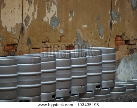 Beer kegs that are double stacked line the wall of a former storefront. The inside has a stage, picnic tables and is open air. Large canvas tents help deflect rain.