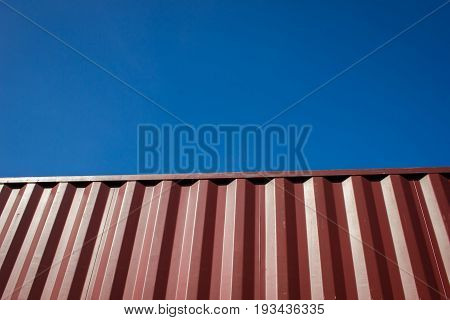 Red cargo container against blue sky for background.