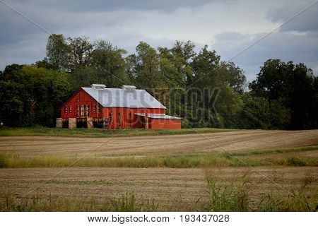 A red barn with doors open to cure air dried tobacco. This is a typical late summer sight in westen Kentucky.