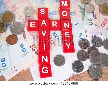 Earn saving concept banknotes and coins thai baht money with keyword by red tag