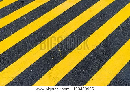 Asphalt Background With Diagonal Black And Yellow Warning Stripes