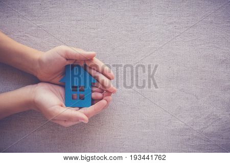 hands holding paper house homeless shelter and real estate concept