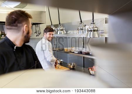 cooking food, profession and people concept - happy male chef and cook with knife chopping champignons on cutting board at restaurant kitchen