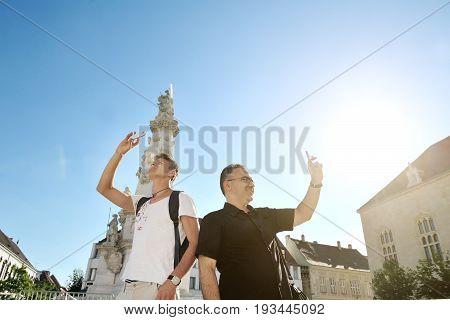 Budapest Hungary Europe - two tourists taking pictures with cellphone in a sunny day
