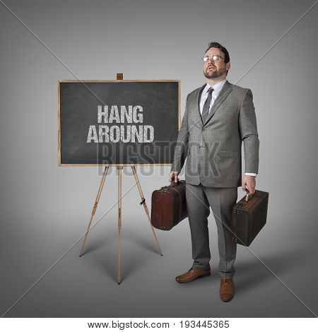 Hang around text on  blackboard with businessman carrying suitcases