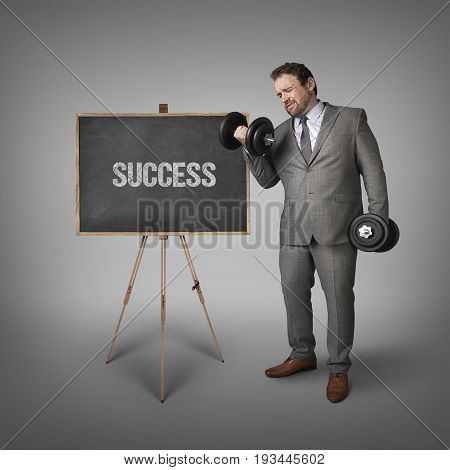 Success text on blackboard with businessman holding weights