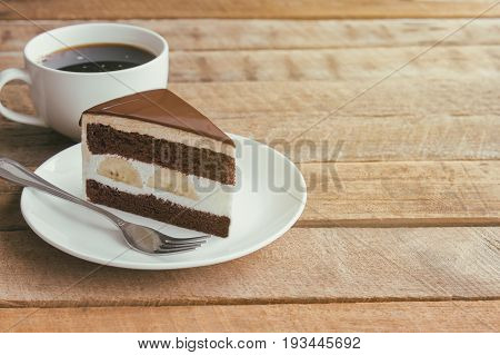 Banana chocolate cake on white plate served with black coffee. Chocolate cake layered with whipped cream and banana look so delicious. Enjoy eating at cafe restaurant with chocolate cake and coffee. Triangle slice piece of chocolate cake.