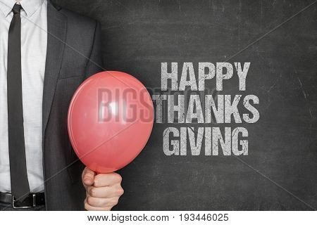 Midsection of businessman holding red balloon with happy thanksgiving text on chalkboard
