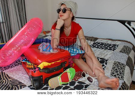 pretty young woman in hat with suitcase. Happy young woman in colorful summer outfit sitting near the red staffed suitcase