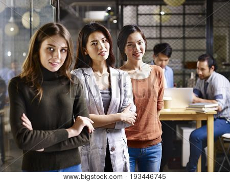 portrait of three asian and caucasian businesswomen focus on person in the middle.