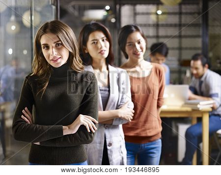portrait of three asian and caucasian businesswomen focus on foreground.